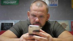 Brodaty młody przypadkowy mężczyzna używa mobilny telefonu komórkowego ono uśmiecha się szczęśliwy Młody i zdrowy mężczyzna ono u zdjęcie wideo