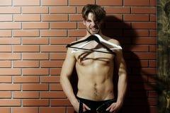Brodaty mięśniowy macho mężczyzna modniś z seksownym ciałem trzyma wieszaki Fotografia Royalty Free