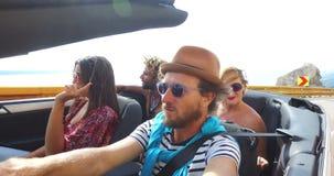 Brodaty modnisia mężczyzna jeżdżenie w kabriolecie na wijącej autostradzie z przyjaciółmi zdjęcie wideo