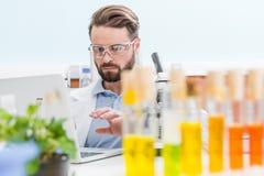 Brodaty naukowiec pracuje z laptopem w laboratorium zdjęcie stock