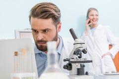 Brodaty naukowiec pracuje z mikroskopem i laptopem w laboratorium obraz royalty free