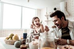 Brodaty przystojny pozytywny mężczyzna w białym koszulowym łasowaniu ma śniadanie z jego żoną fotografia stock