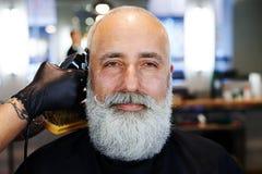 Brodaty przystojny starszy mężczyzna w zakładzie fryzjerskim Fotografia Stock