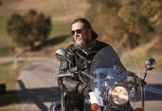 Brodaty rowerzysta siedzi na nowożytnym motocyklu z długie włosy w czarnych okularach przeciwsłonecznych i skórzanej kurtce zdjęcie royalty free