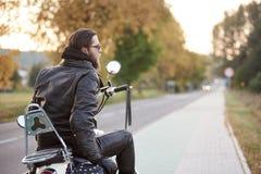 Brodaty rowerzysta w czarnej skórzanej kurtce na nowożytnym motocyklu na kraju poboczu zdjęcia royalty free