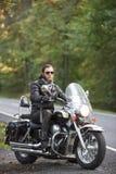 Brodaty rowerzysta w czarnej skórzanej kurtce na nowożytnym motocyklu na kraju poboczu obrazy royalty free