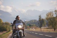 Brodaty rowerzysta w czarnej sk?rzanej kurtce na nowo?ytnym motocyklu na kraju poboczu zdjęcie royalty free