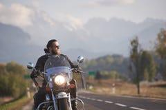 Brodaty rowerzysta w czarnej sk?rzanej kurtce na nowo?ytnym motocyklu na kraju poboczu obraz royalty free