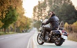 Brodaty rowerzysta w czarnej sk?rzanej kurtce na nowo?ytnym motocyklu na kraju poboczu obraz stock