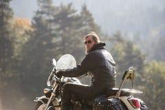 Brodaty rowerzysta z długie włosy w czarnym skórzanej kurtki obsiadaniu na nowożytnym motocyklu zdjęcia stock