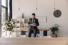 Brodaty skoncentrowany biznesmen używa cyfrową pastylkę w nowożytnym biurze zdjęcia royalty free