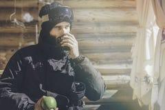 Brodaty szczęśliwy snowboarded bierze odpoczynek po przejażdżki sesi Młody człowiek pije filiżankę gorąca herbata na pogodnym tar zdjęcie royalty free