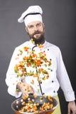 Brodaty szef kuchni podrzuca warzywa w smaży niecce Fotografia Stock