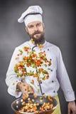 Brodaty szef kuchni podrzuca warzywa w smaży niecce Zdjęcia Stock