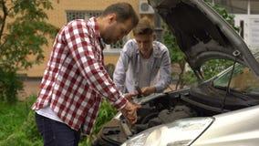 Brodaty tata i jego syna naprawiania samochód z otwartym kapiszonem outdoors, naprawianie silnik zdjęcie wideo