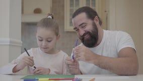 Brodaty tata i piękna mała córka siedzi przy stołem na dniu wolnym malujemy z flamasters Rozrywka ojciec i zbiory wideo