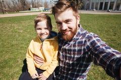 Brodaty uśmiechnięty ojciec outdoors z jego małym synem Zdjęcie Stock