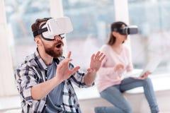 Brodaty uradowany mężczyzna próbuje dotykać VR przedmioty zdjęcie royalty free