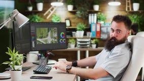 Brodaty videographer pracuje na podwójnym parawanowym ustawianiu w wygodnym loft eviroment zbiory
