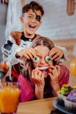 Broder och barn som känner sig roliga, medan äta tematiska sötsaker för allhelgonaafton arkivbild