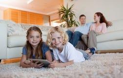 Broder och dotter som använder tableten på matta Royaltyfri Bild