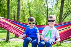 Broder och pojke som kopplar av i h?ngmatta p? semestern arkivbilder
