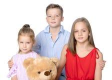 Broder och två systrar med en nallebjörn Royaltyfria Bilder