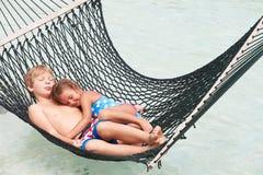 Broder And Sister Relaxing i strandhängmatta royaltyfri bild