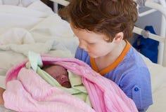 Broder som möter den nyfödda systern Arkivbild