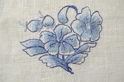 Broderad flowerför blått för satänghäftklammerpå bomullstorkduken Arkivbild