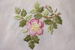 Broderad rosa flowerför satänghäftklammerpå bomullstorkduken Arkivbild
