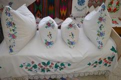 Broderade kuddar är på sängen royaltyfria foton