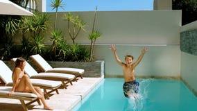 Broderdykning in i simbassängen, medan systern håller ögonen på honom stock video