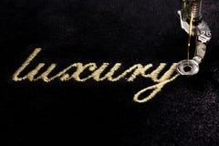 broderi av guld- bokstäver & x22; luxury& x22; på svart sammetslent tyg Arkivfoto