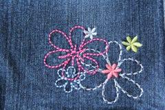 Trådda blommor på jeans Arkivbild