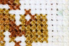 Broderi för tråd för brunt för modell för broderi för makroskottfragment handgjord, modell i korsstygnstil på vitt tyg Arkivfoto