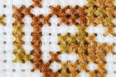 Broderi för tråd för brunt för modell för broderi för makroskottfragment handgjord, modell i korsstygnstil på vitt tyg Royaltyfria Bilder