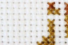 Broderi för tråd för brunt för modell för broderi för makroskottfragment handgjord, modell i korsstygnstil på vitt tyg Fotografering för Bildbyråer
