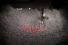 broderia czerwona literowanie sprzedaż na miękkiej części popielatej tkaninie z hafciarską maszyną - odgórny widok z poruszającym zdjęcie royalty free