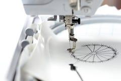 broderie avec la machine de broderie - dandilon sur le similicuir blanc Photos stock