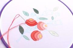 Broderie avec le motif floral encadrée dans un cercle Travail dans le procédé Photos stock