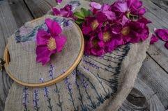 Broderie de travail manuel et fleurs d'un dogrose Images stock