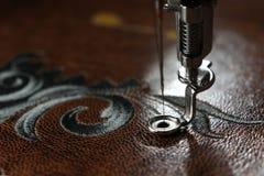 Broderie multicouche sur le similicuir brun avec la machine de broderie - fermez-vous avec l'aiguille  Photo stock