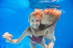 Brodern kramar och kysser hans syster under vatten royaltyfri fotografi