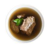 Brodo di manzo con carne in una ciotola bianca, isolata sopra bianco immagini stock