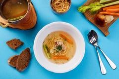 Brodo di pollo con le tagliatelle e le verdure del fungo Minestra leggera su un fondo blu Fotografie Stock