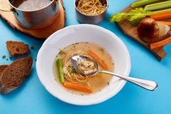 Brodo di pollo con le tagliatelle e le verdure del fungo Minestra leggera su un fondo blu Immagini Stock