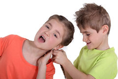 Broer die het haar van de zuster trekken stock foto's