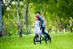 Broer die zijn zuster op een fietsrit neemt stock afbeelding