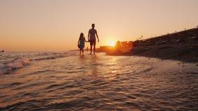 Broer en jongere zuster die langs de kust bij zonsondergang lopen stock videobeelden